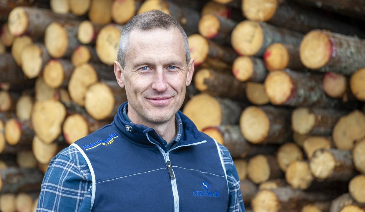 Portrait of Göran Sundberg standing infront of a pile of timber.