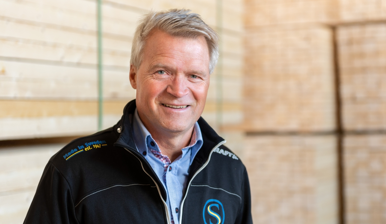 Portrait of our salesperson Göran Ejnestrand, standing infront of packages of sawn wood.