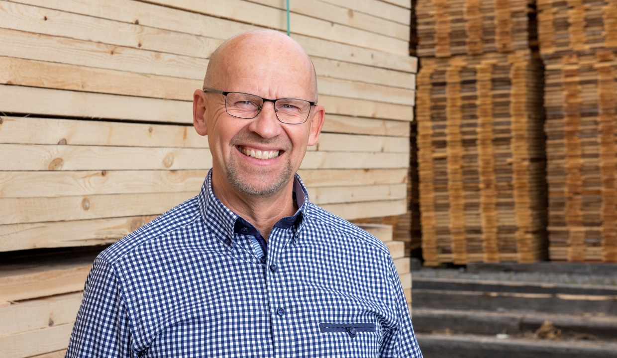 Portrait of our salesperson Håkan Carlzon, standing infront of packages of sawn wood.
