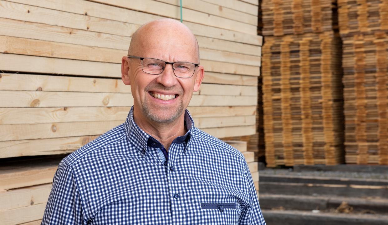 Porträttbild på vår säljare Håkan Carlzon som står framför sågade virkespaket.