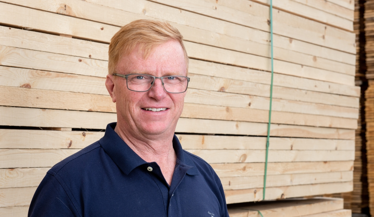 Portrait of our salesperson Thord Fjällström, standing infront of packages of sawn wood.